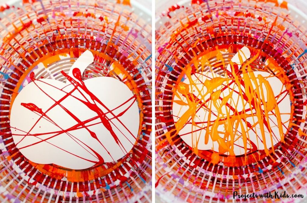 Orange and red paint drizzled onto pumpkin template in a salad spinner for spin painting art