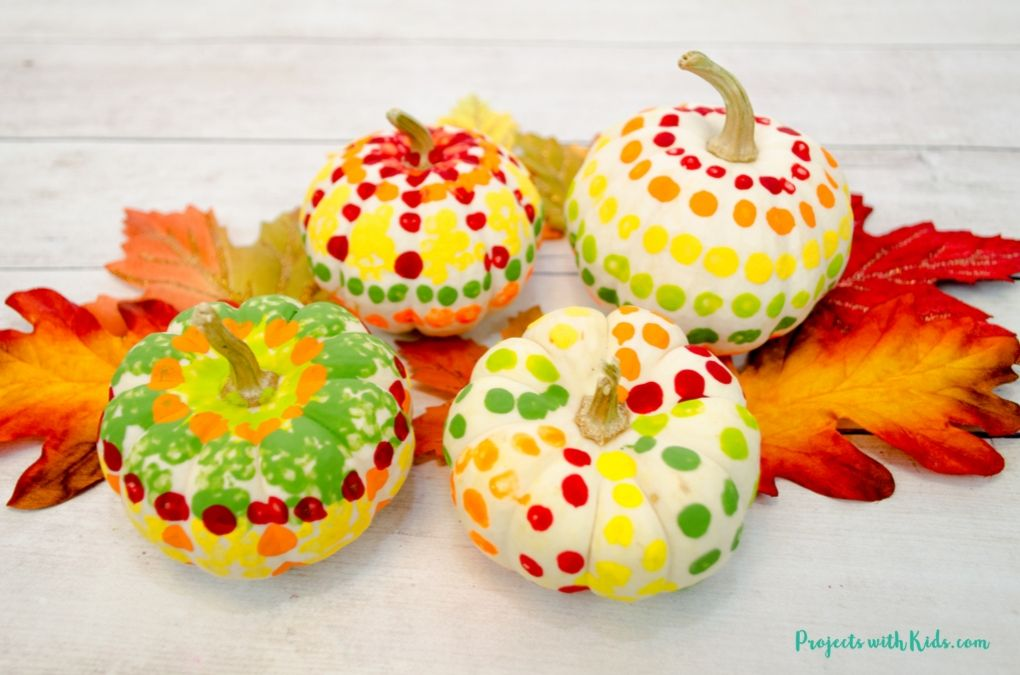 q-tip painted pumpkins arranged on fall leaves