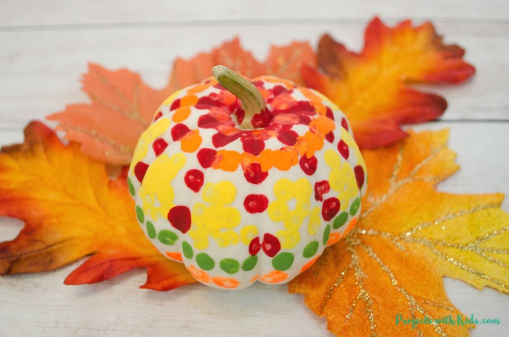 Mini painted white pumpkin on fall leaves for a Thanksgiving table centerpiece