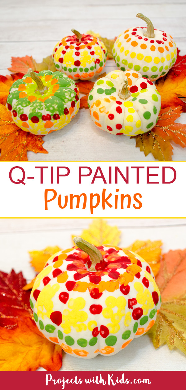 Q-tip painted pumpkins using mini white pumpkins placed on fall leaves