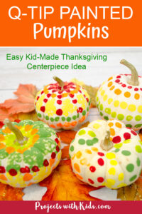 Mini white pumpkins with dots on them painted with q-tips on fall leaves for a kid-made Thanksgiving centerpiece craft.