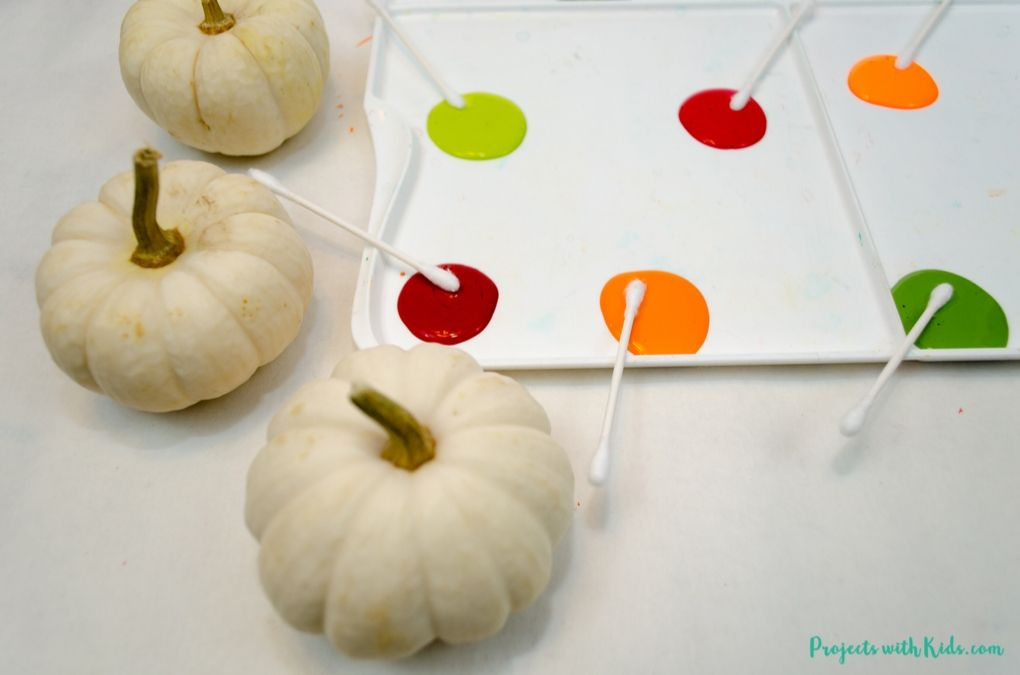 white mini pumpkins, acrylic paint in fall colors on a paint palette and q-tips