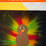 Turkey art project on black paper using orange, red and green chalk pastels and brown, red and yellow cardstock and sticker eyes