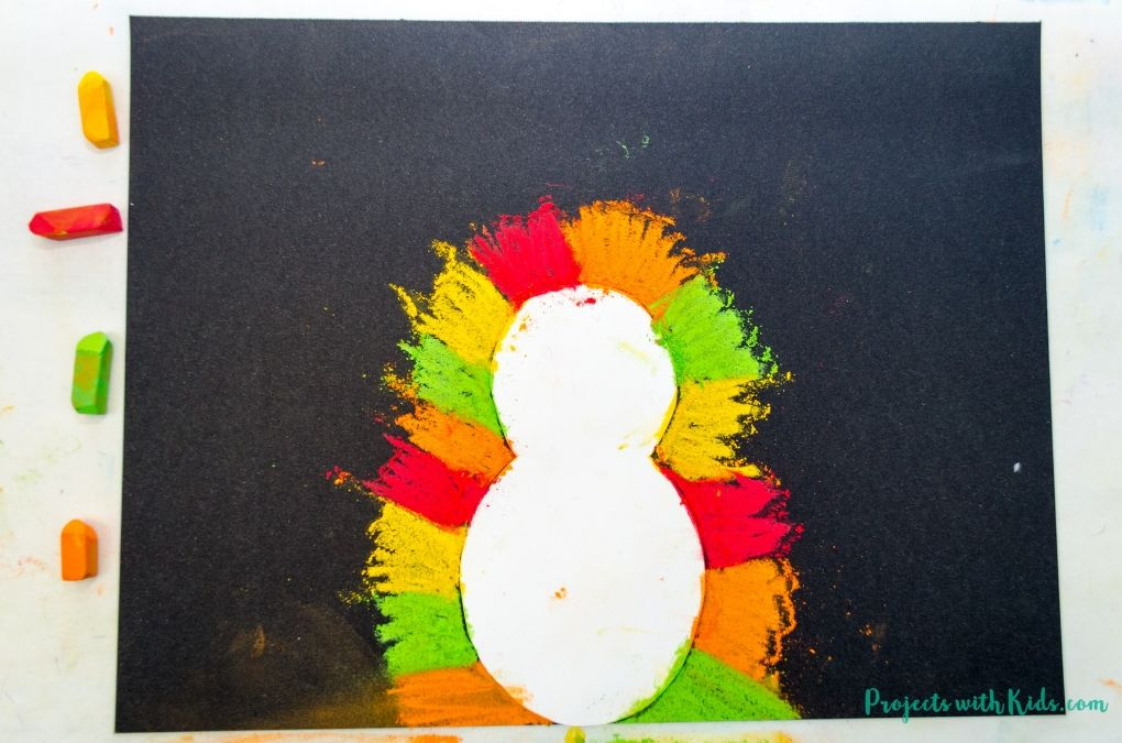 Chalk pastels drawn around a turkey template on black paper
