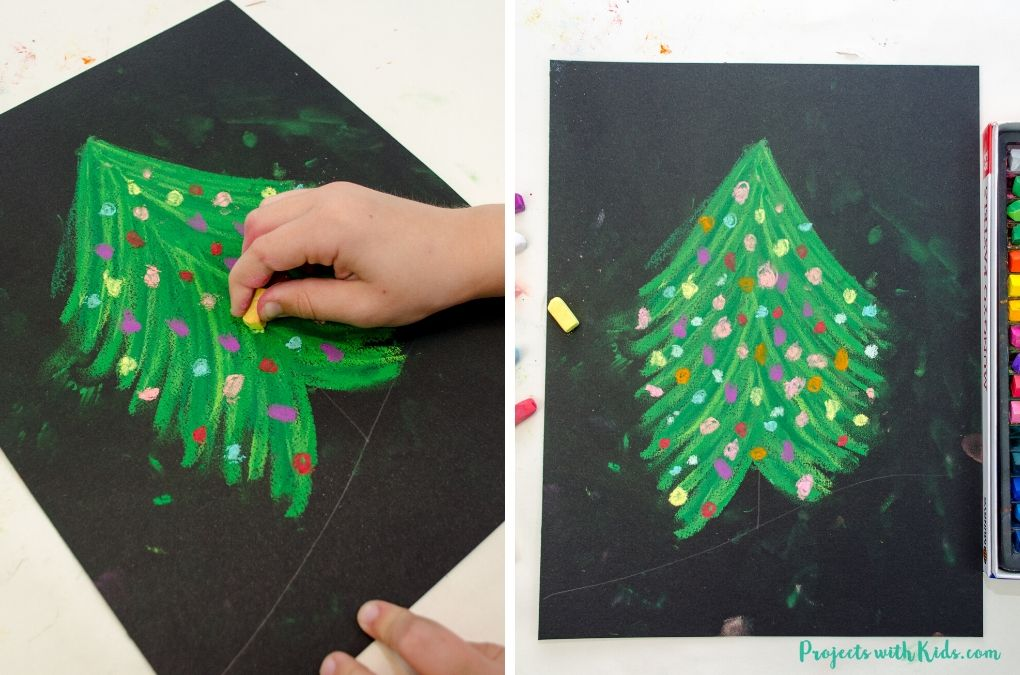 Drawing decorations onto a chalk pastel christmas tree on black paper