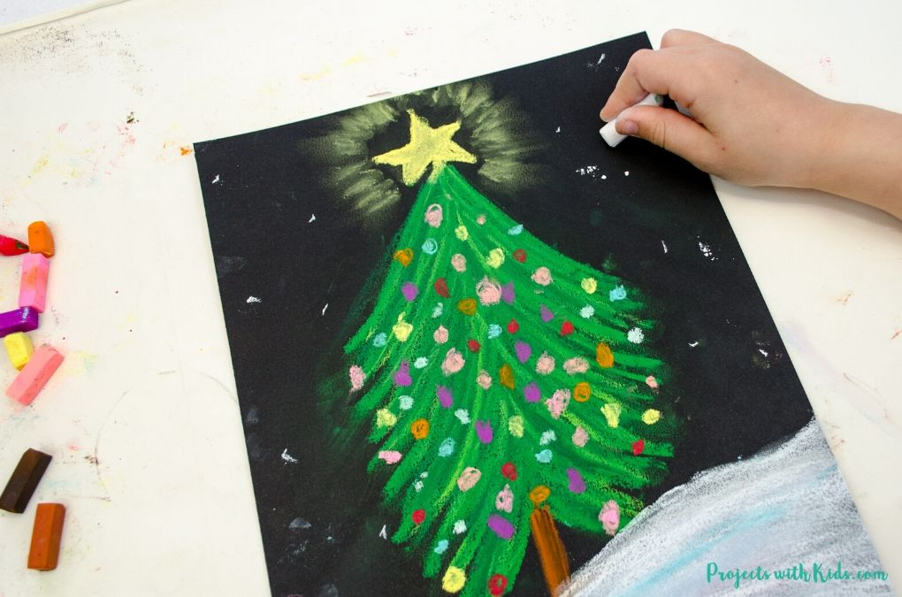 Drawing snowflakes on black paper with white chalk pastel.