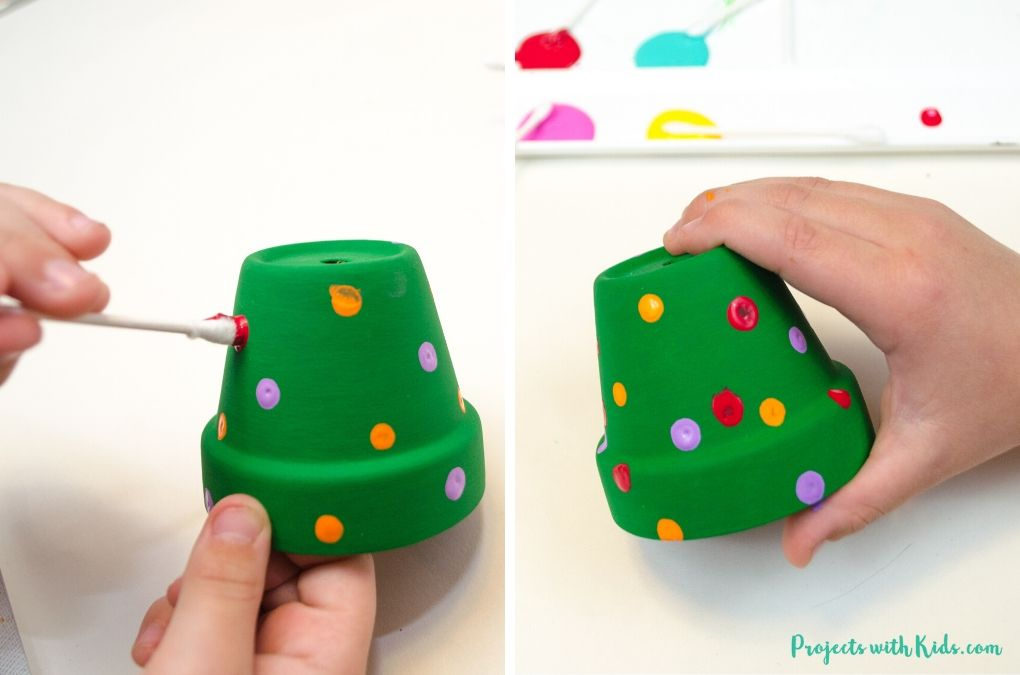 Painting with q-tips dot decorations on mini clay pots for a Christmas tree ornament craft.