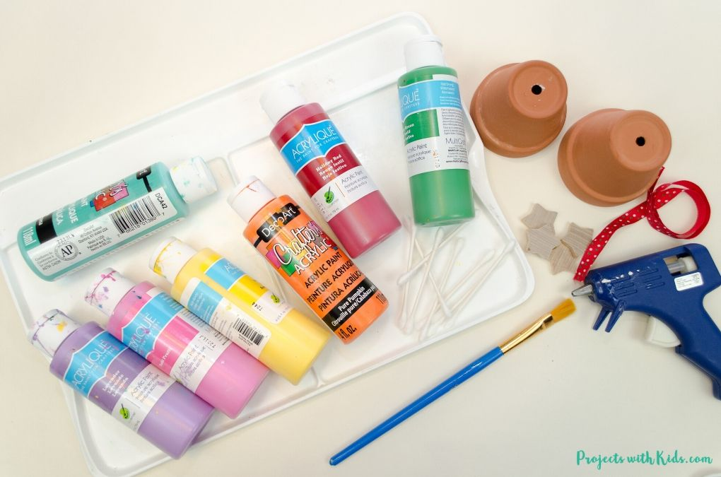 Acrylic paint, paint palette, paintbrush, mini clay pots, wooden stars, glue gun, ribbon
