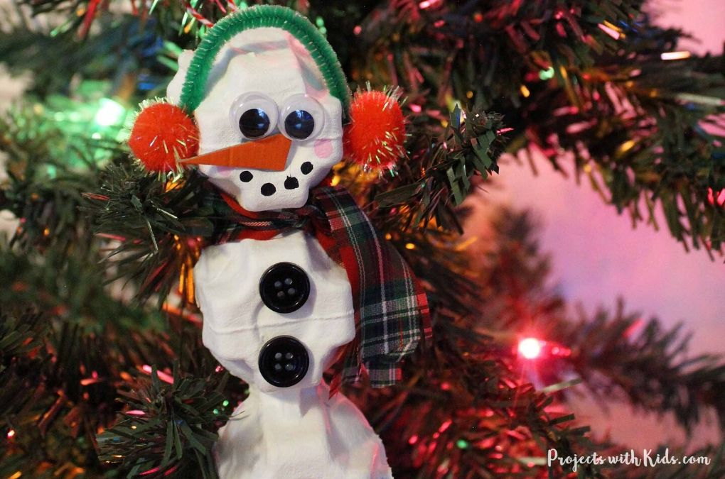 Snowman egg carton ornament hanging on a Christmas tree.