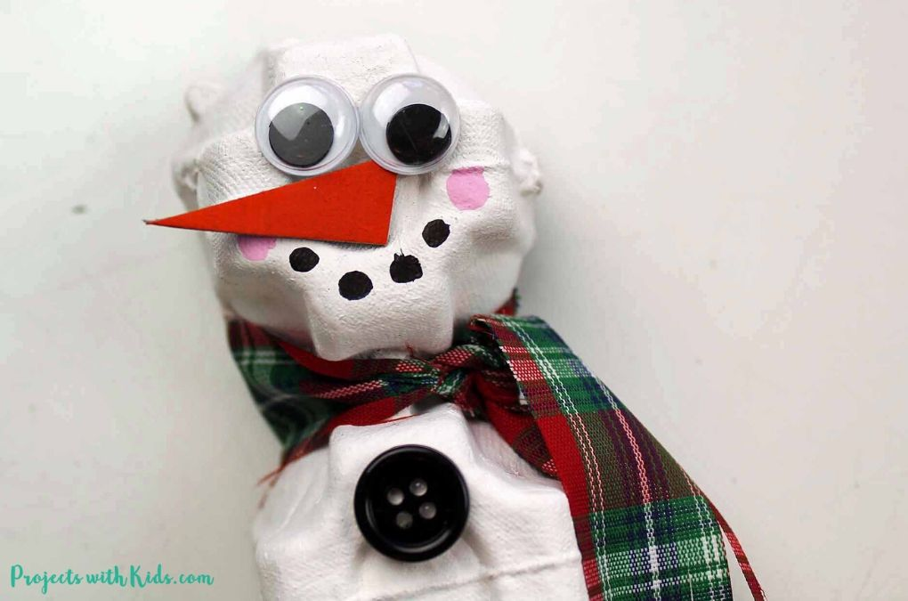 Adding a face to an egg carton snowman craft for kids