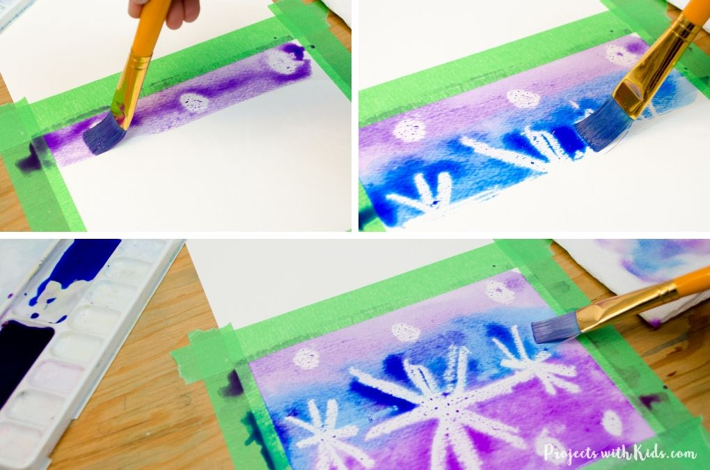 Painting with blue and purple watercolor paint to reveal a snowflake resist design.