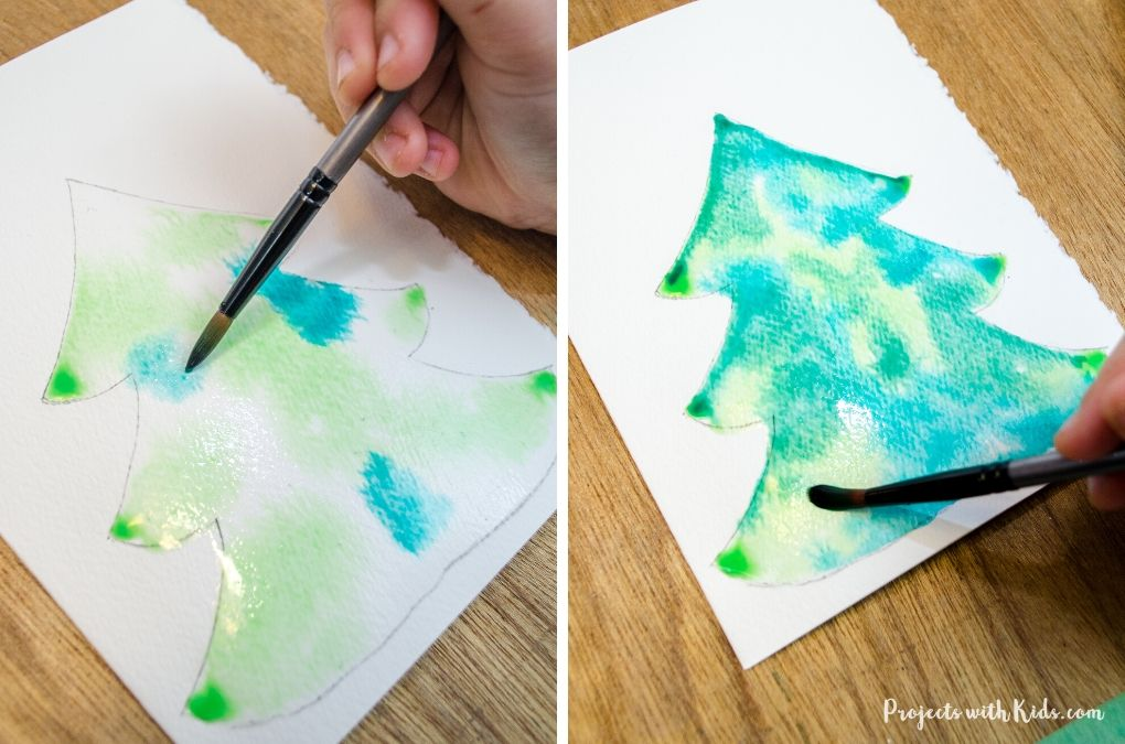Painting green watercolors on a christmas tree watercolor card.