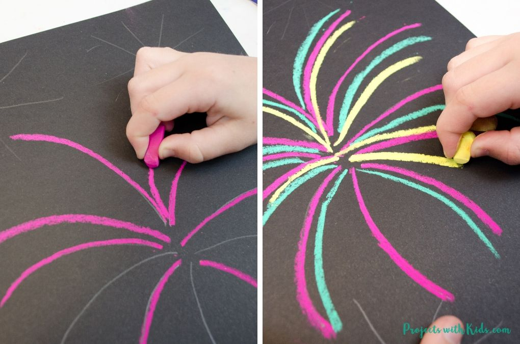 Drawing pink and yellow on black paper to make fireworks art.