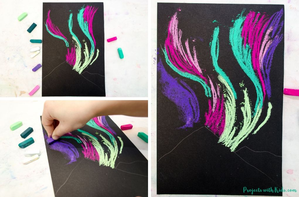 Drawing the northern lights with chalk pastels on black paper.