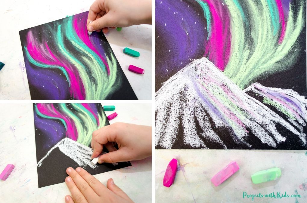 Adding snow covered mountains to a northern lights chalk pastel art project.