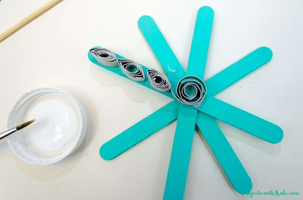 Glueing paper quills onto a popsicle snowflake