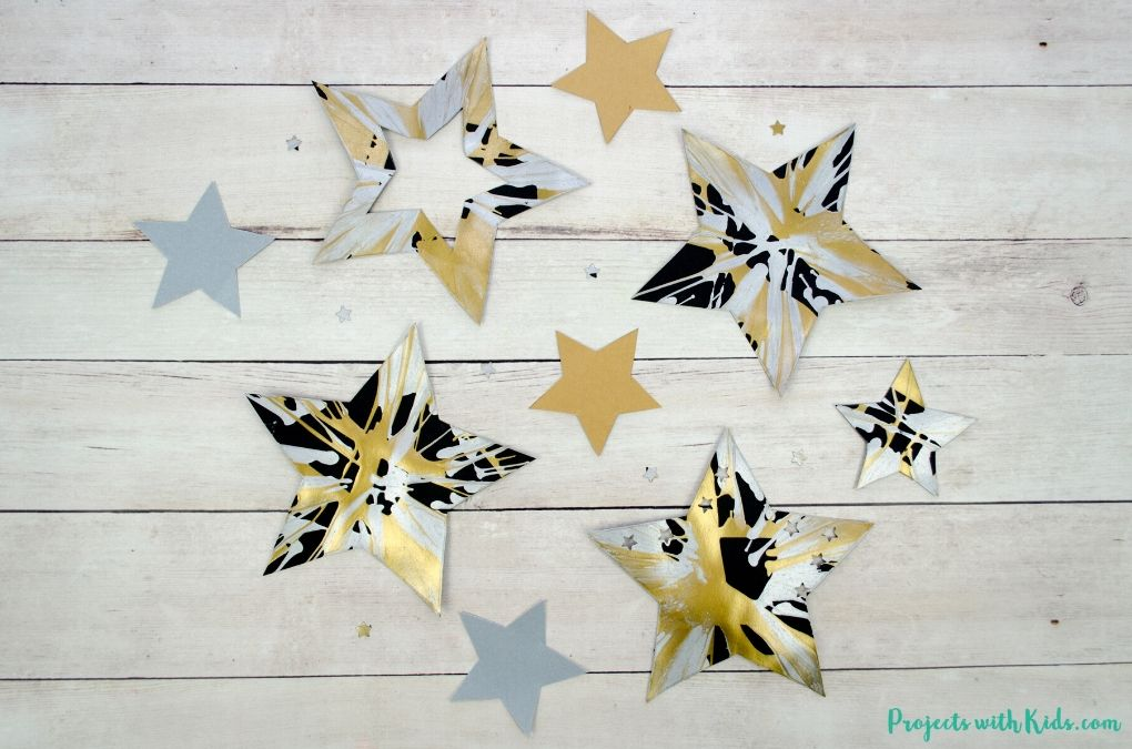 Spin painted stars art project on black paper with gold and silver paint.