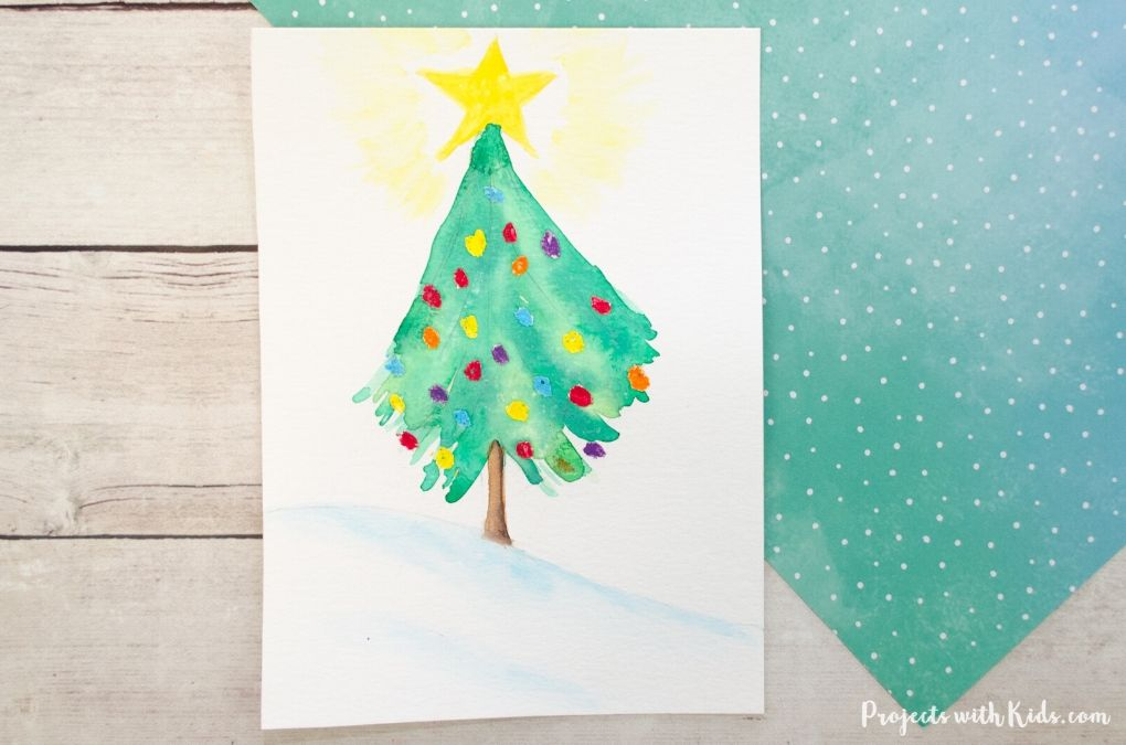 Christmas tree art using watercolor paint and oil pastels.