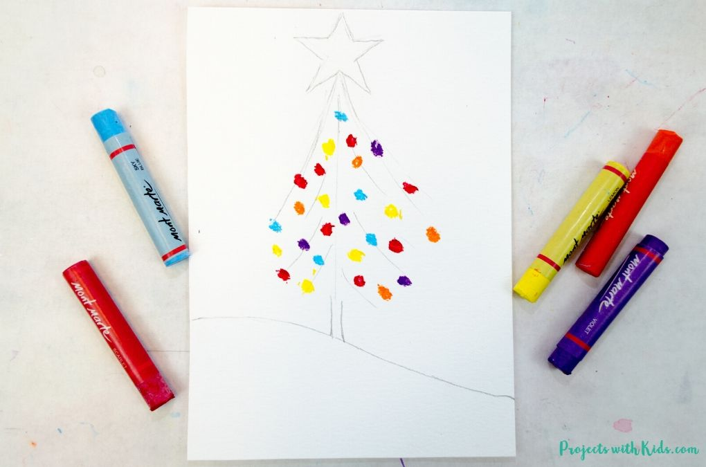 Drawing oil pastel Christmas tree decorations onto watercolor paper.
