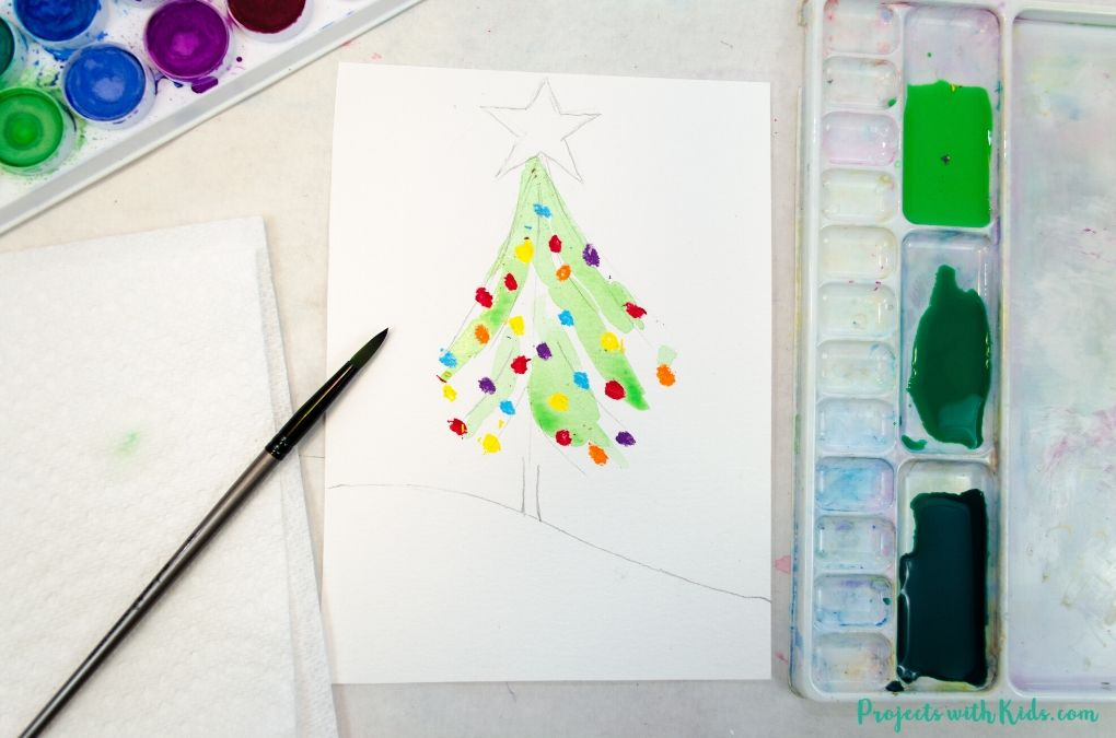 Painting green watercolor on paper to paint a watercolor Christmas tree.