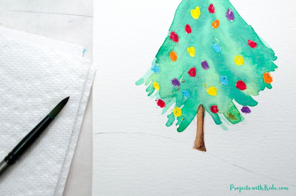 Painting a tree trunk on a Christmas tree art project.