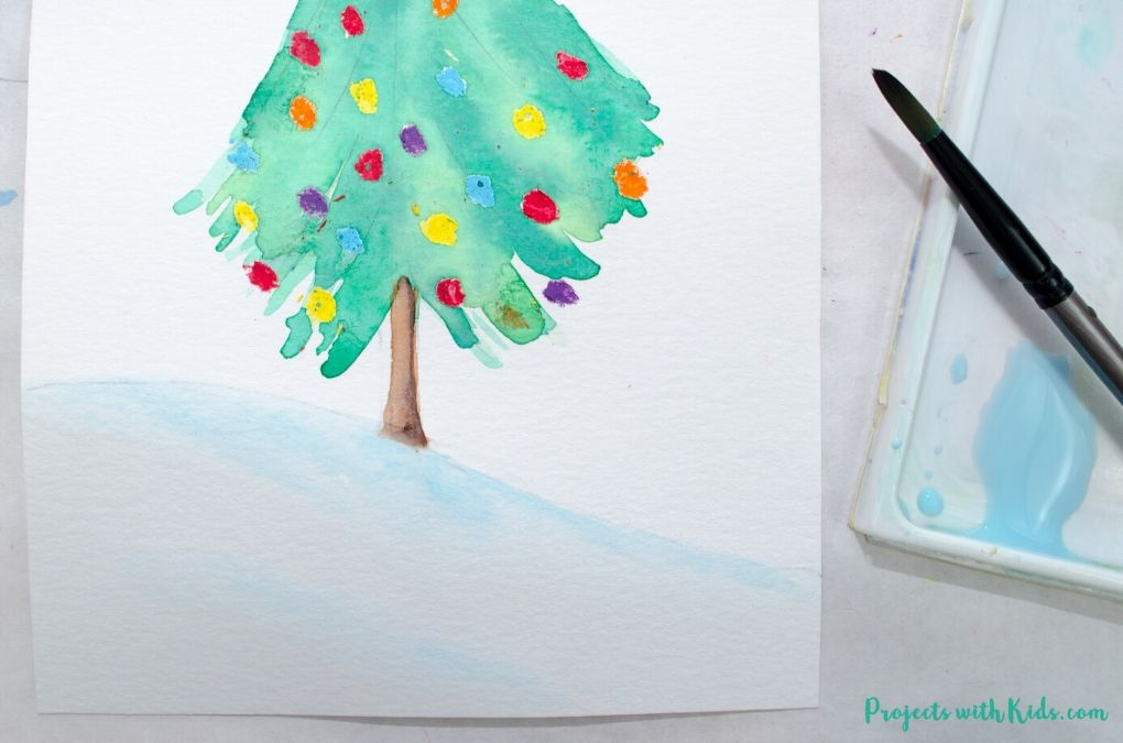 Painting light blue shadows on a snowy hill with watercolor paint.