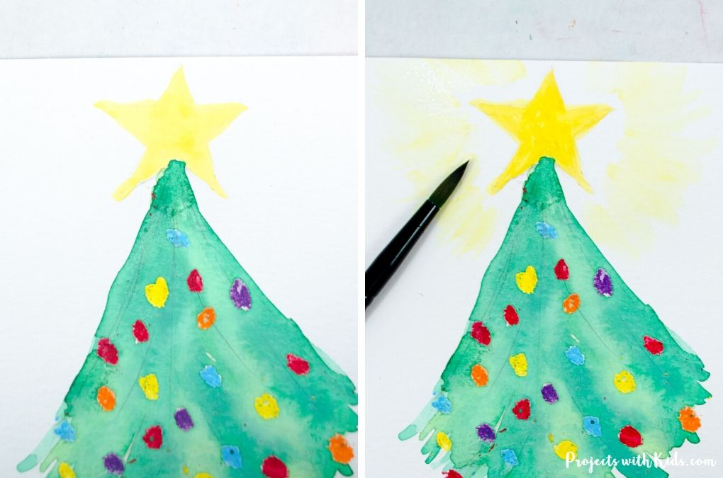 Painting a watercolor star at the top of a Christmas tree.