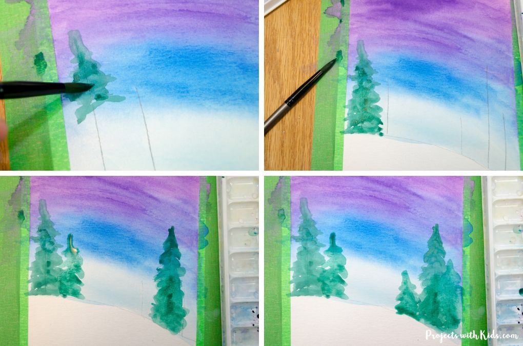 Painting evergreen trees in a winter art project.