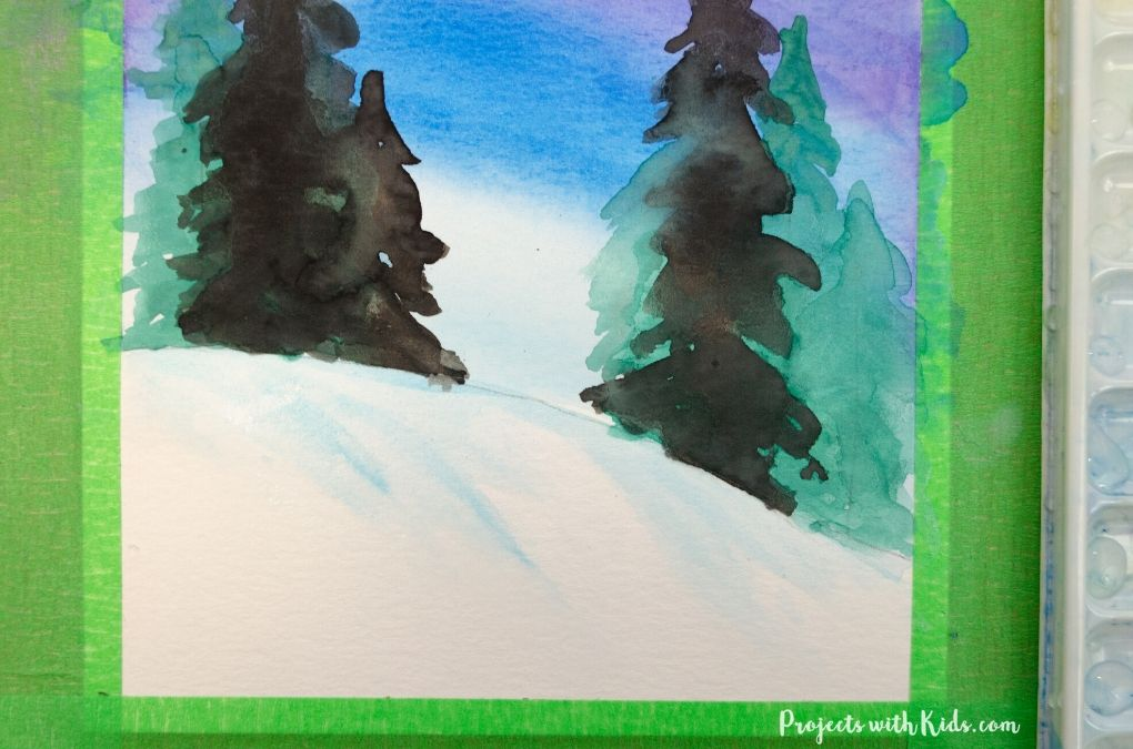 Adding light blue shadows onto a snowy hill in a winter art project for kids.