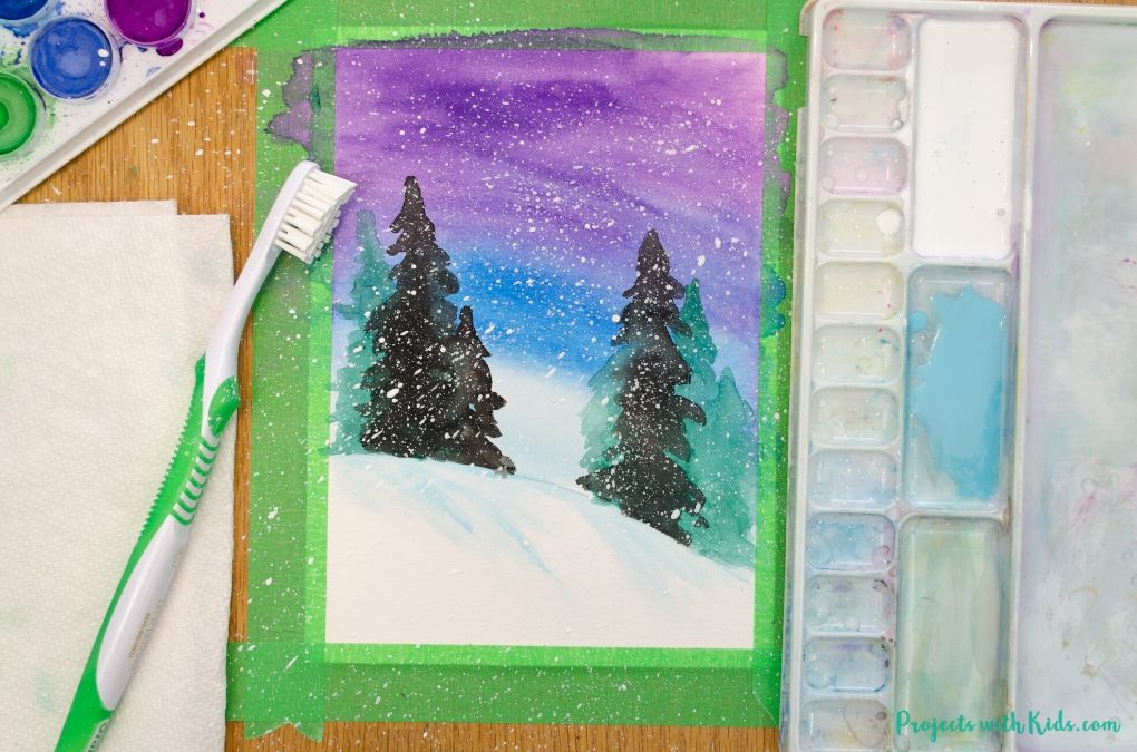Splattering snow with white acrylic paint and a toothbrush onto a watercolor winter painting.