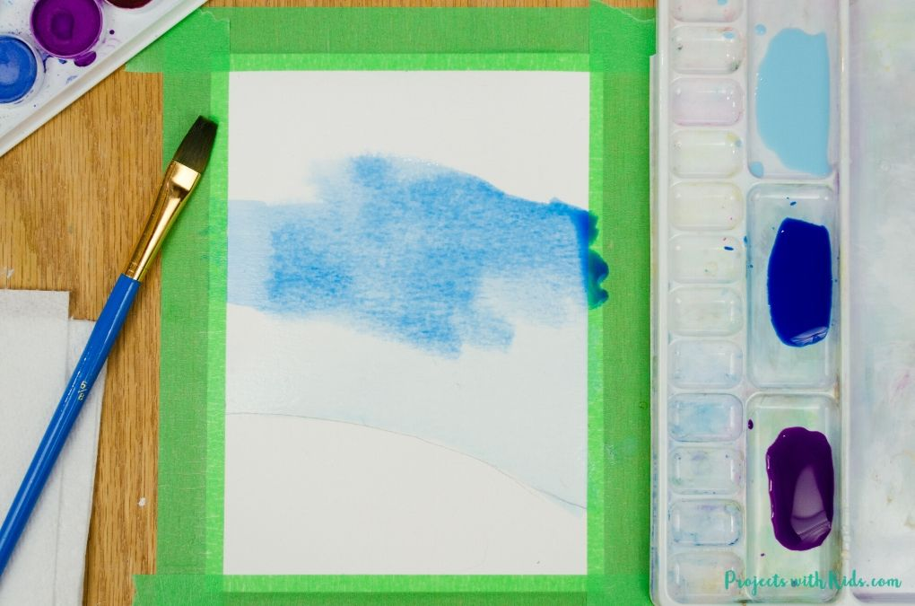 Painting a blue sky with watercolor paint.