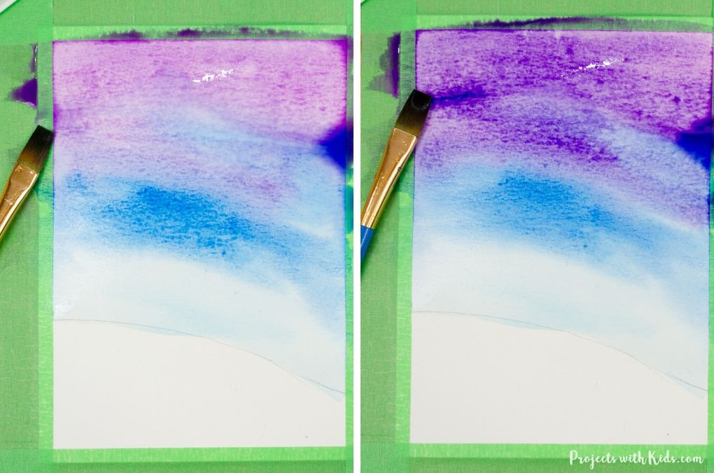 Painting a winter sky with purple watercolor paint.