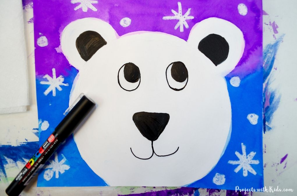 Finishing adding details with a black paint pen to a polar bear face art project for kids