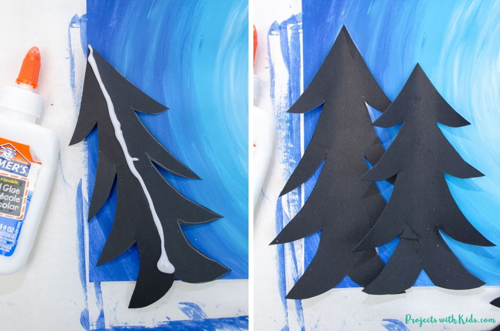 Gluing paper trees onto a winter sky background.