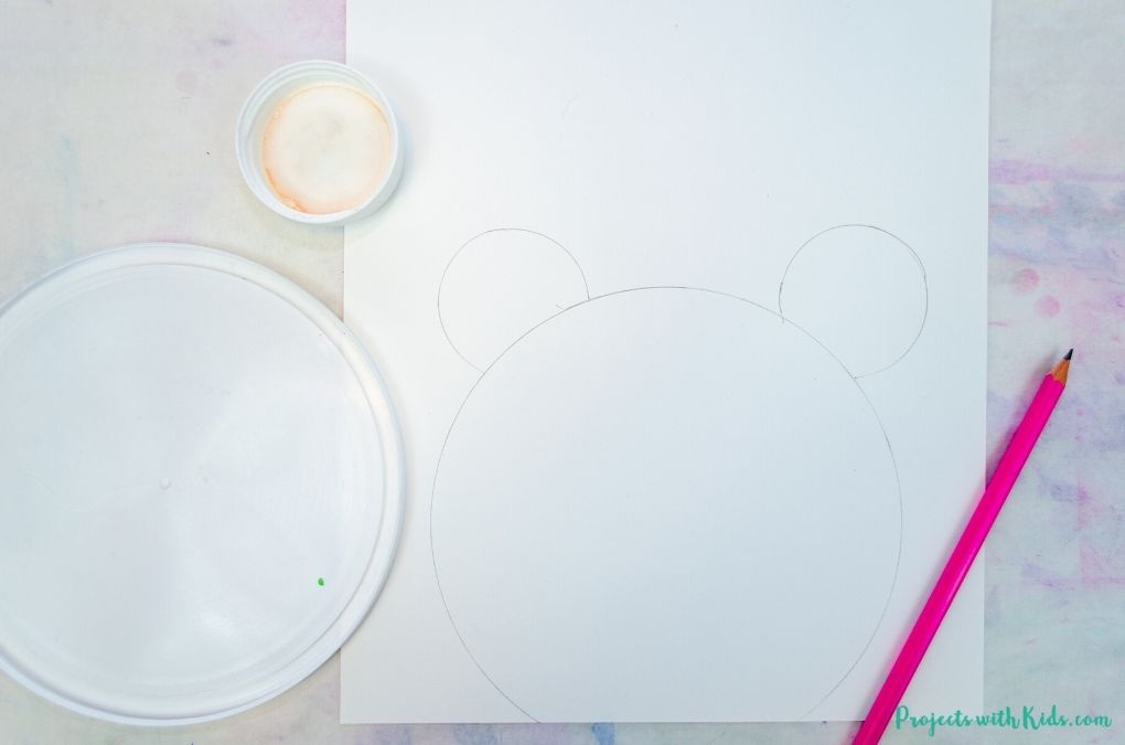 Using plastic lids as a template to draw a panda bear face