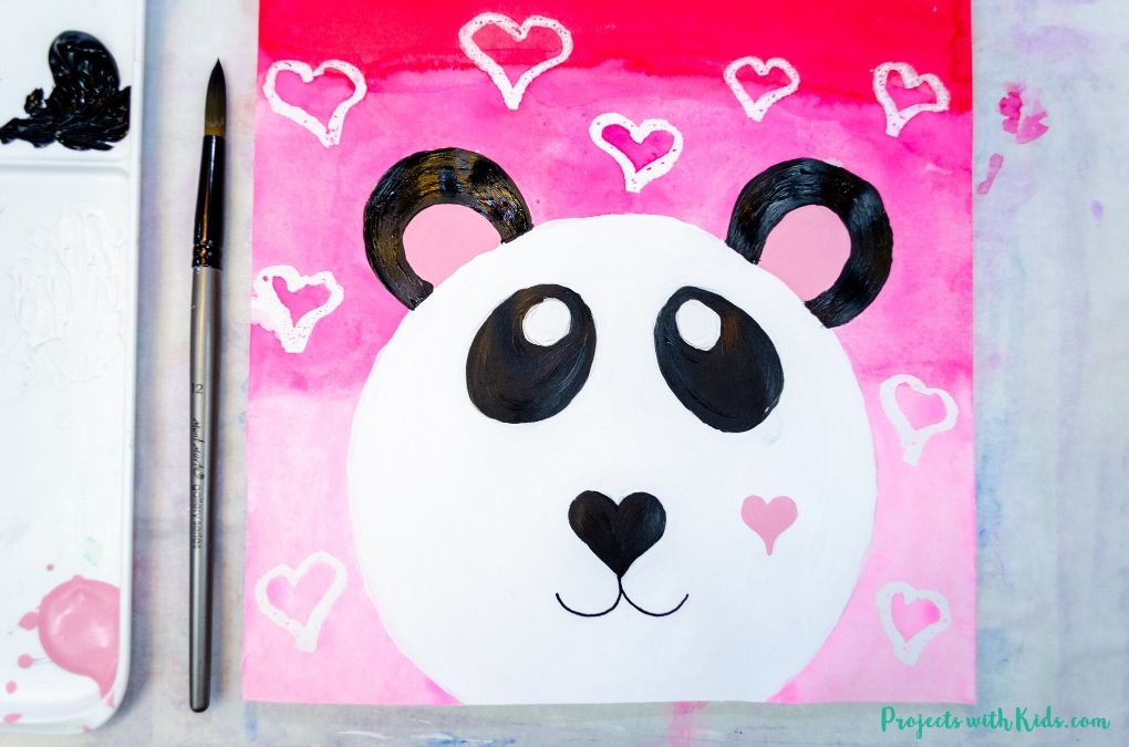 Painting panda bear ears with black acrylic paint.