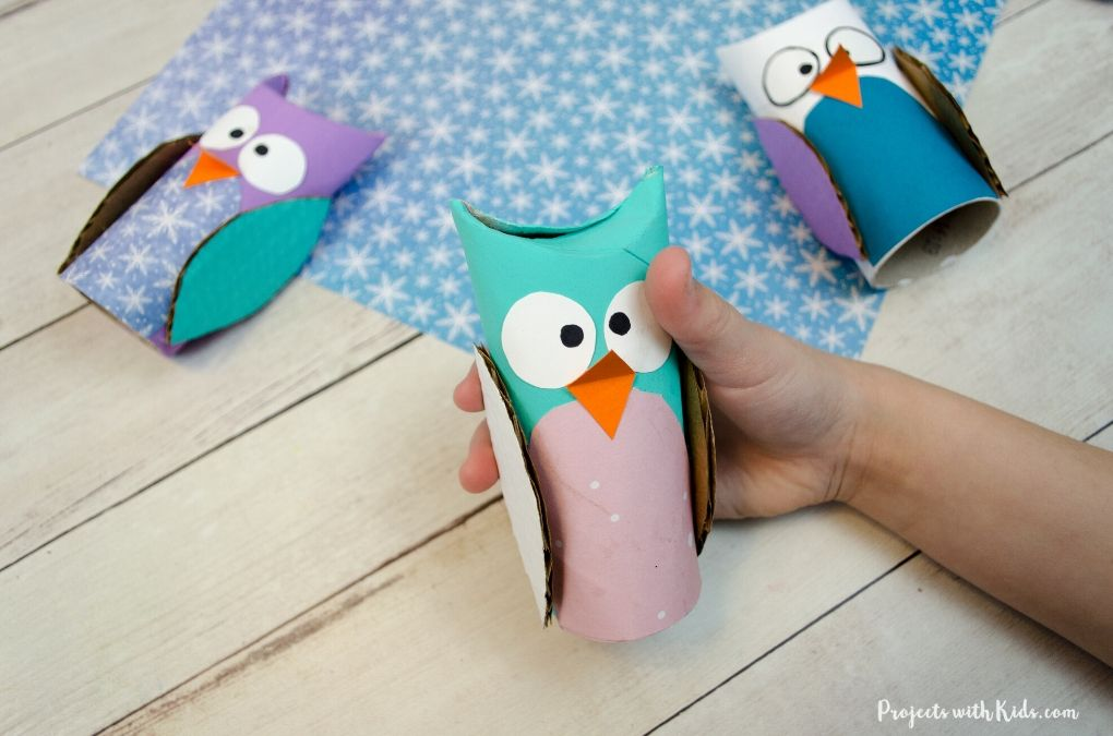 Hand holding a paper owl craft made with toilet paper rolls.