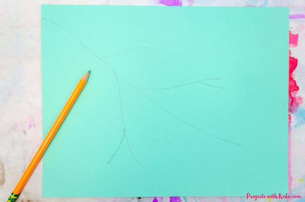 Drawing a tree branch on blue scrapbook paper