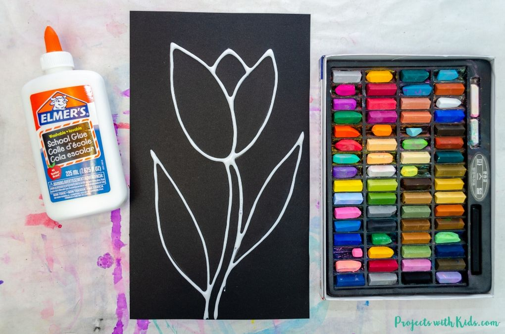 Tracing a tulip drawing on black paper with white glue.
