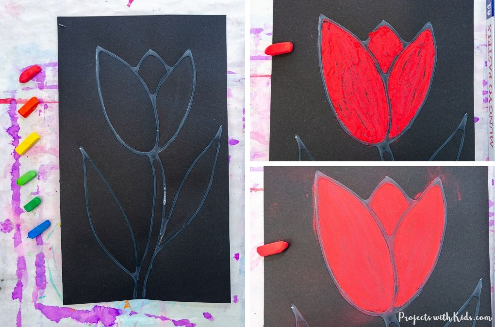 Coloring in a tulip with red chalk pastel on black paper