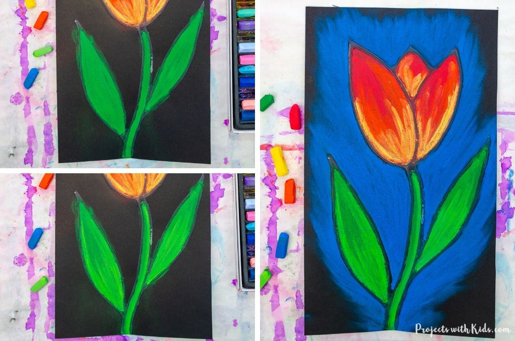 Drawing tulip leaves and a blue background with chalk pastels on black paper.
