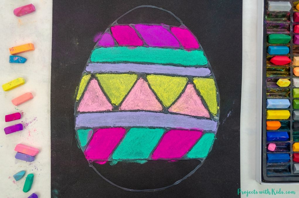 Coloring an Easter egg with chalk pastels on black paper.