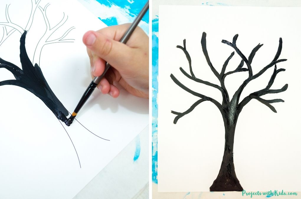 Painting a tree with black acrylic paint.