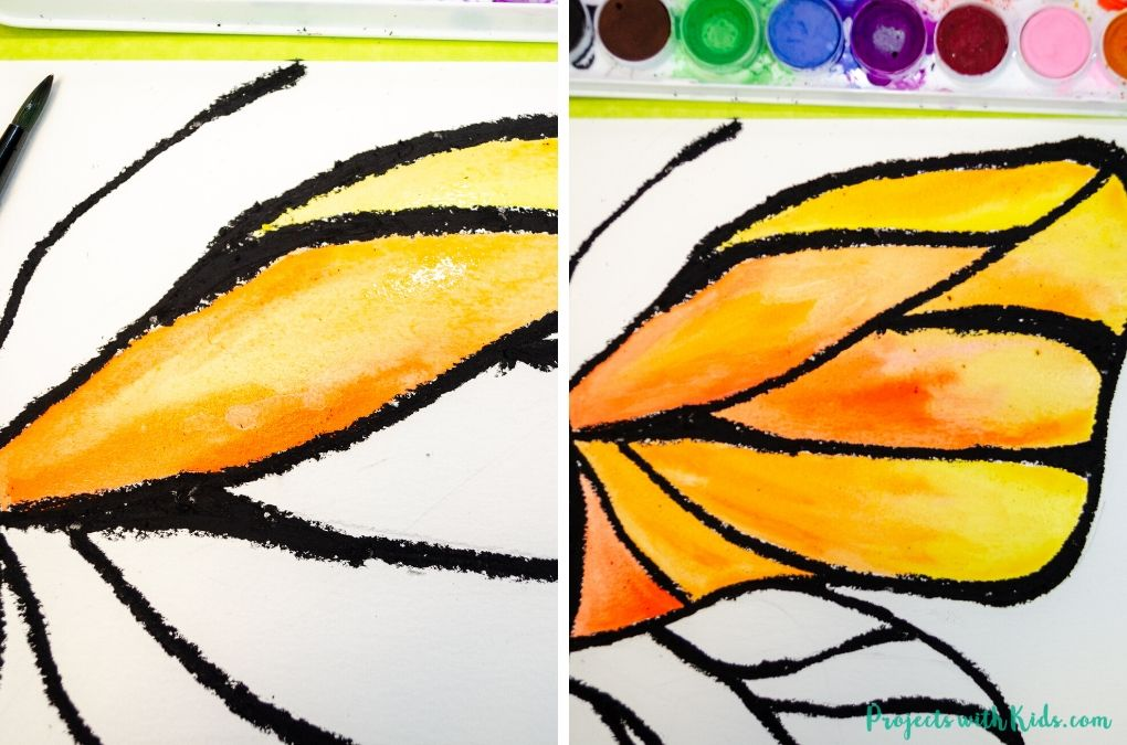 Painting butterfly wings with orange and yellow watercolor paint.