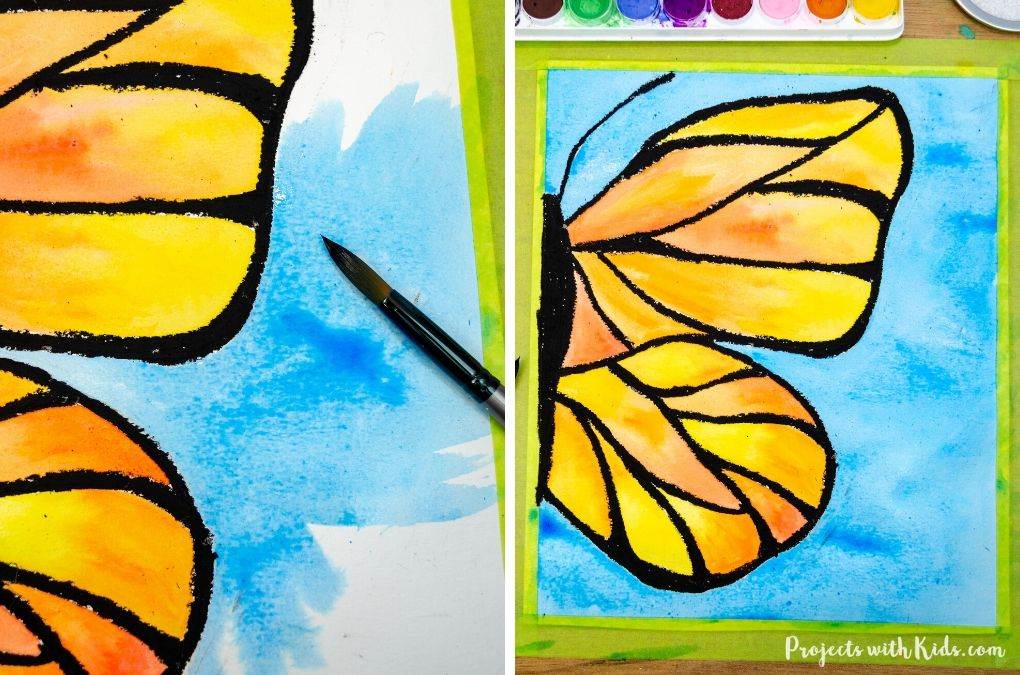 Painting the background of a butterfly painting with blue watercolor paint using a wet on wet technique..