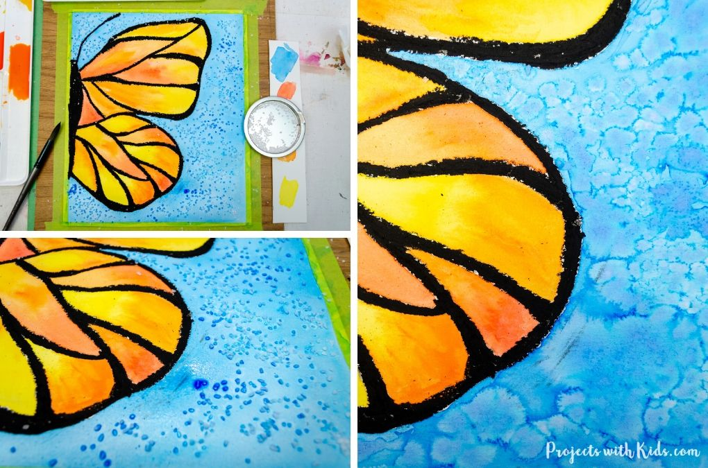 Sprinkling salt onto a wet watercolor painting of a butterfly.