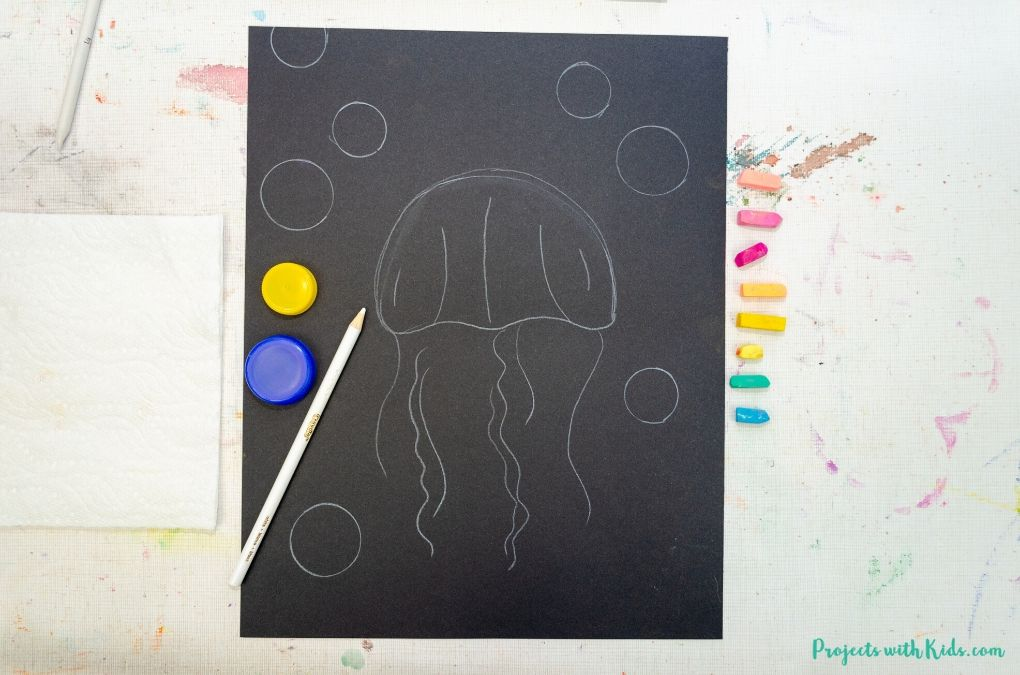 Drawing a jellyfish on black paper.