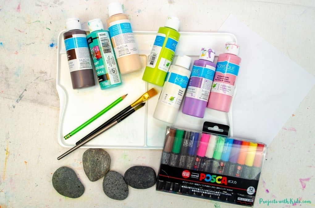 Rock painting art supplies including acrylic paint, paint brushes, paint pens and rocks