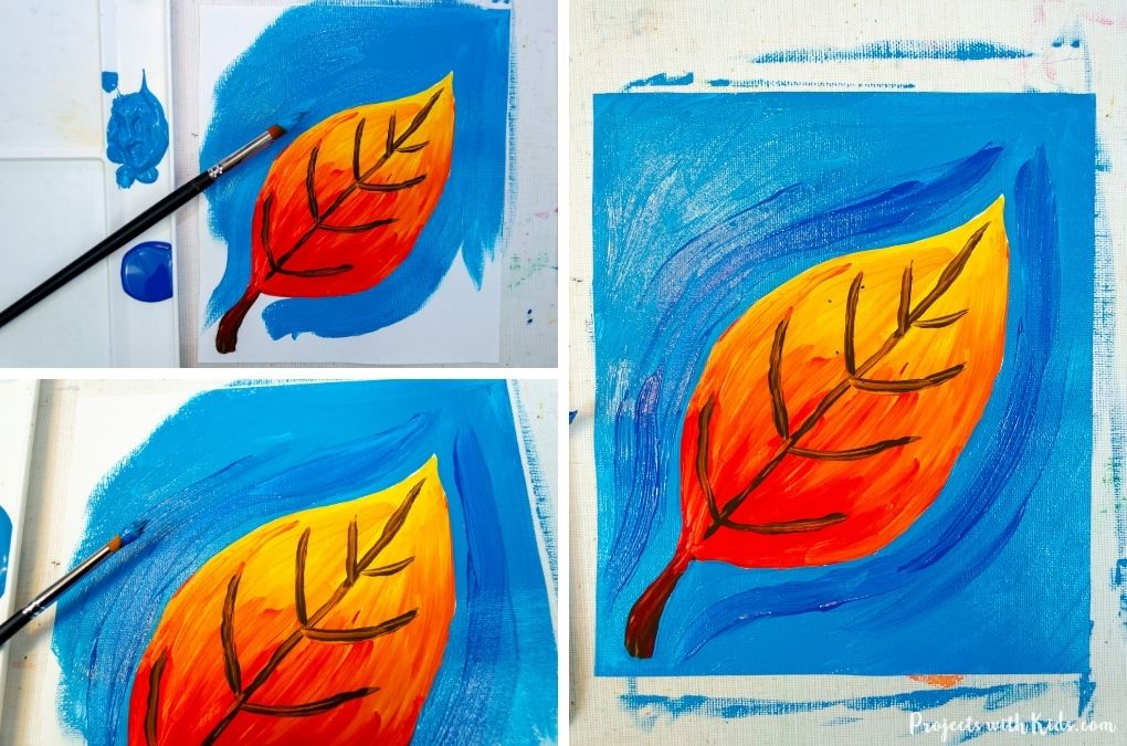 Painting a blue background on a fall leaf painting.
