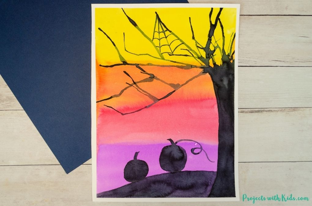Halloween painting with spooky tree and pumpkin silhouettes